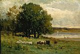 cattle near river with sailboat in distance